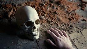 De dalende hand van een dode verslaafde met een spuit tegen de achtergrond van de schedel langzame motie stock videobeelden