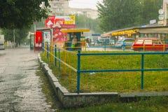 De daling die van het regenwater aan het oppervlaktewater op straat vallen Stock Afbeeldingen