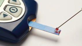 De daling van bloed syringed op teststrook van glucosemonitor stock videobeelden