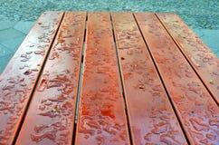 De daling van het Clloseupwater op een houten lijst stock foto's
