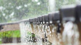 De daling van regendalingen onophoudelijk van een dak in het regenachtige seizoen stock video