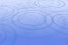 De dalingen die van de regen tot rimpelingen in water leiden Stock Foto's