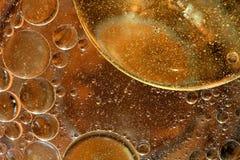 De dalingen van de olie op een waterspiegel stock foto