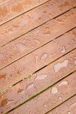 De Dalingen van de regen op hout Stock Foto's