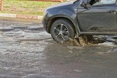 De dalingen van het autowiel in een diep gat stock foto's