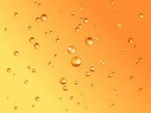 De dalingen van het bier in sinaasappel backgroun Stock Afbeeldingen