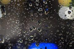 De dalingen van het regenwater op glas Stock Foto