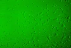 De dalingen van het textuurwater op het groene flessenclose-up als achtergrond Stock Foto