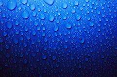 De dalingen van het water op blauw glas in dark Royalty-vrije Stock Foto