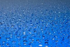 De dalingen van het water op een glanzende oppervlakte stock foto's