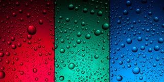 De dalingen van het water op rood, groen en blauw stock fotografie