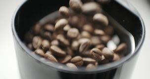 De dalingen van koffiebonen in de molen stock videobeelden