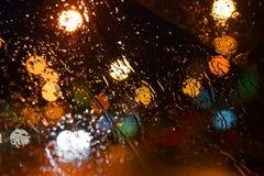 De dalingen van de regen op het venster De stad van de Bokehnacht Royalty-vrije Stock Fotografie
