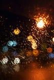 De dalingen van de regen op het venster De stad van de Bokehnacht Stock Foto's