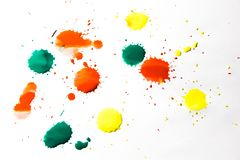 De dalingen van rode, gele en groene verf worden bespoten op een witte achtergrond stock foto
