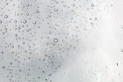 De dalingenachtergrond van het water Waterdalingen op glasvenster over blauwe sk Stock Afbeeldingen