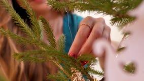De dame bekijkt gouden sneeuwvlok op de nieuwe langzame motie van de jaarboom stock video