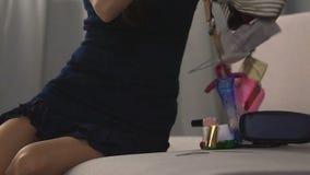 De dame die inhoud van haar zak op bank uitgieten die haar mobiele telefoon zoeken, knoeit stock video
