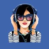 De dame in glazen met oortelefoons luistert aan muziek Royalty-vrije Stock Foto