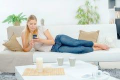 De dame legde op laag gebruikend cellphone royalty-vrije stock afbeelding
