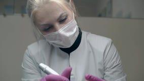 De dame met blonde paardestaart past permanente wenkbrauwsamenstelling toe stock footage