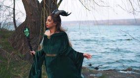 De dame met lang donker vliegend haar bevindt zich in elegante dure velor smaragdgroene kleding met open schouder, een meisje met stock videobeelden