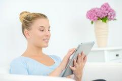 De dame zat thuis gebruikend tablet stock foto