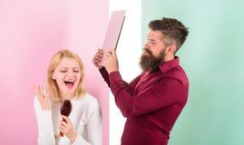 De dame zingt het gebruiken van haarborstel als microfoon terwijl geërgerde de mens het gaan haar laptop sloeg Zing beter bij tal royalty-vrije stock afbeelding