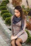De dame zit op de rand en stelt aan fotograaf De herfstphotosession Stock Foto