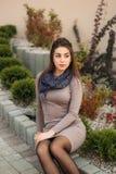 De dame zit op de rand en stelt aan fotograaf De herfstphotosession Royalty-vrije Stock Afbeeldingen