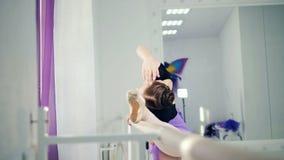 De damedanser rekt zich dichtbij staaf in een balletstudio uit stock video