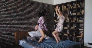 De dames die in de pyjama's over bed springen gelukkig en dat in een moderne zitslaapkamer met stedelijke stijl wordt opgewekt on stock footage