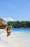 De damezitting van de blonde in water op het strand Royalty-vrije Stock Foto's
