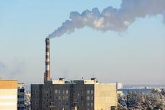 De dampen van de fabrieksschoorsteen over de stad stock foto's