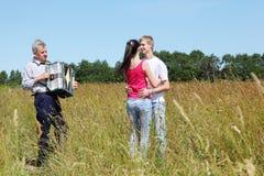 De dans van het paar dichtbij grootvaderspelen op harmonika stock fotografie
