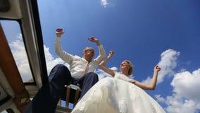 De dansende en golvende handen van het gelukkige jonge vrolijke huwelijkspaar en benen op de retro busbovenkant op het gebied Men stock footage