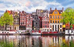 De dansende huizen van Amsterdam Nederland over rivier Amstel stock afbeelding