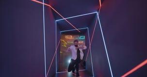 De dansende mensen in de tunnel met kleurenlichten en kosmisch kijken stock footage