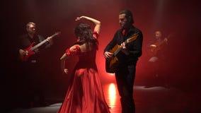 De danser voert bewegingen met haar handen aan de muziek op de gitaar uit Licht van erachter Rook achtergrond stock footage