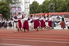 De dansers in traditionele kostuums presteren bij het Grote Volksdansoverleg van Lets de Jeugdlied en Dansfestival in Daugava St royalty-vrije stock foto