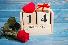 De datum van 14 Februari op kalender, gift, rood hart en nam bloem, het concept van de Valentijnskaartendag toe Royalty-vrije Stock Afbeeldingen
