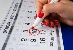De datum wordt omcirkeld met een rode teller in de kalender Stock Foto's