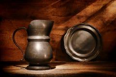 De de antieke Waterkruik en Plaat van het Tin op Oude Houten Plank Royalty-vrije Stock Foto