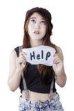 De de behoeftehulp van het tienermeisje en toont een tekst Stock Foto's