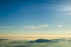 De de blauwe die hemel en mist van bergenwolken van op bergtop wordt gefotografeerd Stock Afbeeldingen