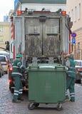 De de dienstarbeiders laadt afval van vuilnisbak aan vuilnisauto Royalty-vrije Stock Fotografie