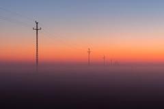 De de elektromachtslijnen en Pylonen verdwijnen over de horizon met Misty Sunrise, Zonsondergang Royalty-vrije Stock Foto's