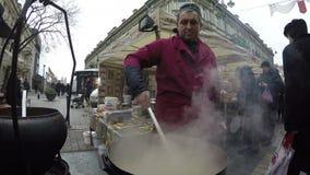 De de erwtensoep van de chef-kokkok in grote pot kookt bij stads vierkante markt 4K stock video