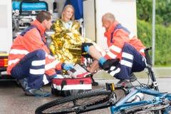 De de fietsvrouw van het ongeval krijgt de paramedici van de noodsituatiehulp Stock Foto's