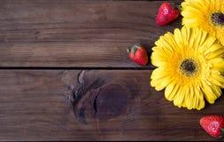 De de gele bloem en aardbei van Gerbera op donkere houten achtergrond Royalty-vrije Stock Foto
